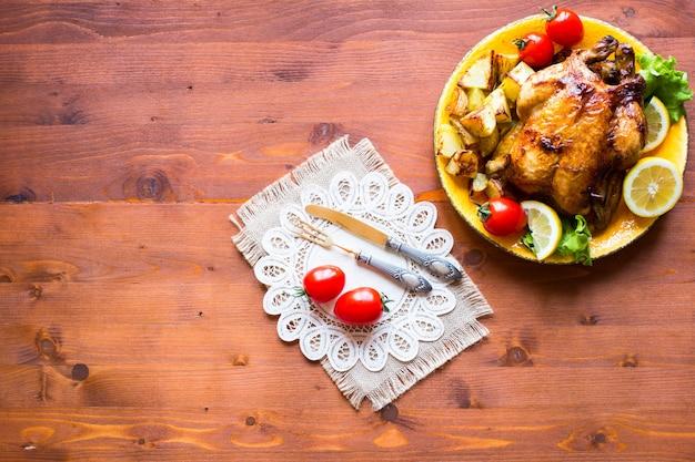 Selbst gemachtes gebackenes huhn mit zitrone und kartoffeln auf einem hölzernen hintergrund