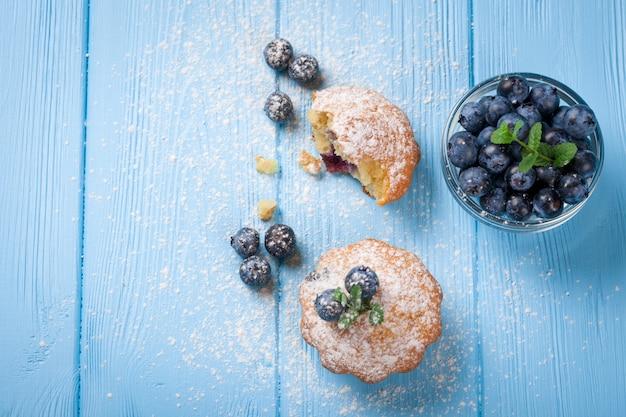 Selbst gemachtes gebackenes muffin mit blaubeeren, frischen beeren, minze, puderzucker auf blauem hölzernem hintergrund. draufsicht leckeres dessert. obst-cupcake bäckerei banner, flyer, karte. leerer platz für text.