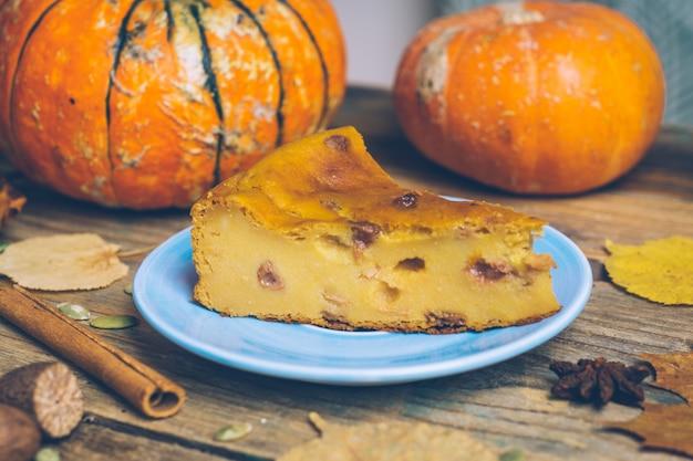 Selbst gemachtes geschnittenes kürbistörtchen-kuchenrezept mit zimt, nüsse auf hölzernem hintergrund. halloween traditioneller nachtisch