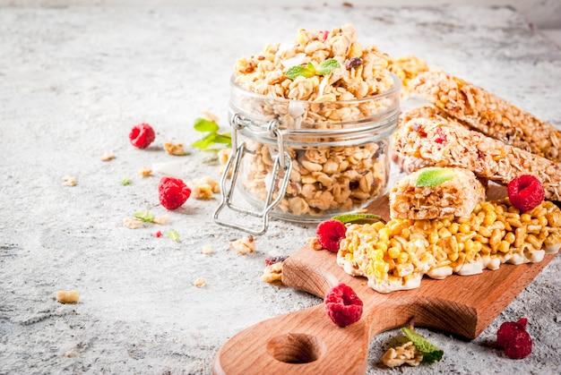 Selbst gemachtes granola des gesunden frühstücks- und snackkonzeptes mit frischen himbeeren im glas und nüsse und müsliriegel auf grauem steinsteinhintergrund