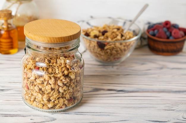 Selbst gemachtes granola im glasgefäß auf holztisch in der küche