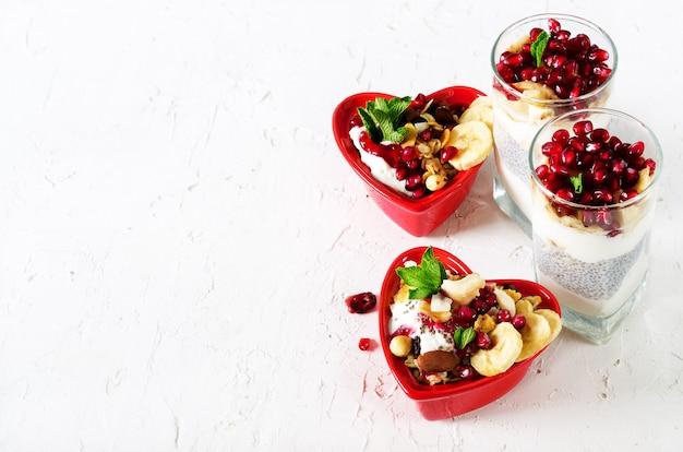Selbst gemachtes granola mit joghurt in der roten herzplatte auf tabelle. romantisches frühstück freiraum für ihren text.