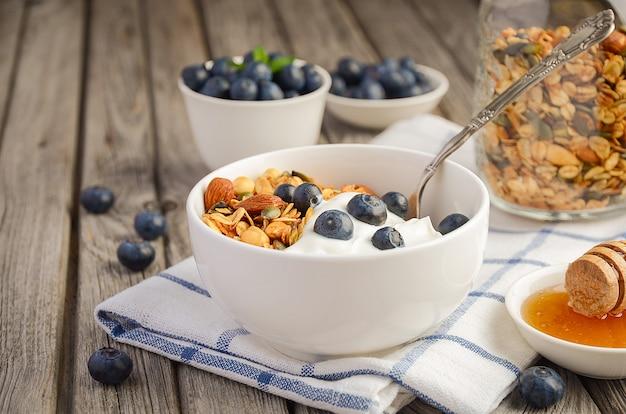 Selbst gemachtes granola mit jogurt und frischen beeren, gesundes frühstückskonzept.