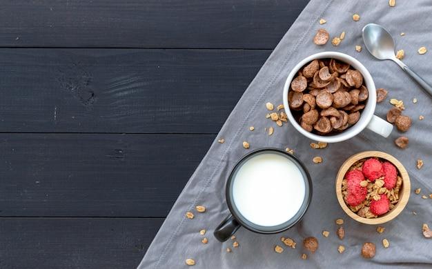 Selbst gemachtes granola mit milch zum frühstück auf holztisch.