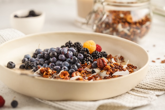 Selbst gemachtes granola mit nüssen und kokosnuss mit beeren und milch in einer weißen platte.