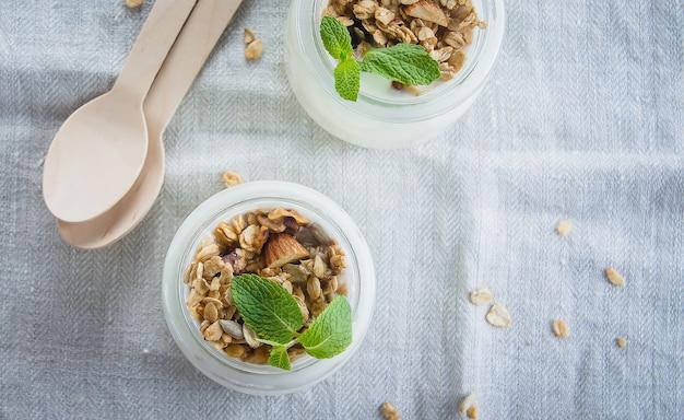 Selbst gemachtes granola mit streifenjoghurt in einem glasgefäß. gesundes essen-konzept