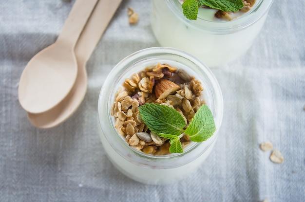 Selbst gemachtes granola mit streifenjoghurt in einem glasgefäß