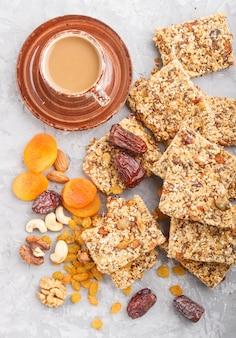 Selbst gemachtes granola vom hafer blättert datteln getrocknete aprikosenrosinen-nüsse mit einem tasse kaffee auf einem grauen konkreten hintergrund ab