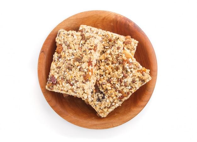 Selbst gemachtes granola von den haferflocken, daten, getrocknete aprikosen, rosinen, nüsse in der braunen hölzernen platte lokalisiert. ansicht von oben.