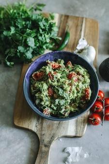 Selbst gemachtes guacamole mit kirschtomatenlebensmittelphotographie-rezeptidee