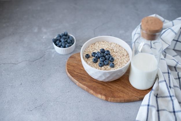 Selbst gemachtes hafermehl mit blaubeeren und erdbeeren in der schüssel auf grauem beton. gesundes frühstück.