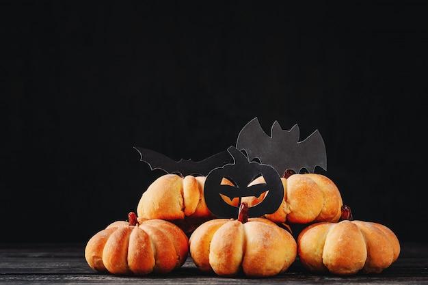 Selbst gemachtes halloween backt in form des kürbises auf dunklem hintergrund mit kopienraum zusammen. hallo halloween süßigkeiten