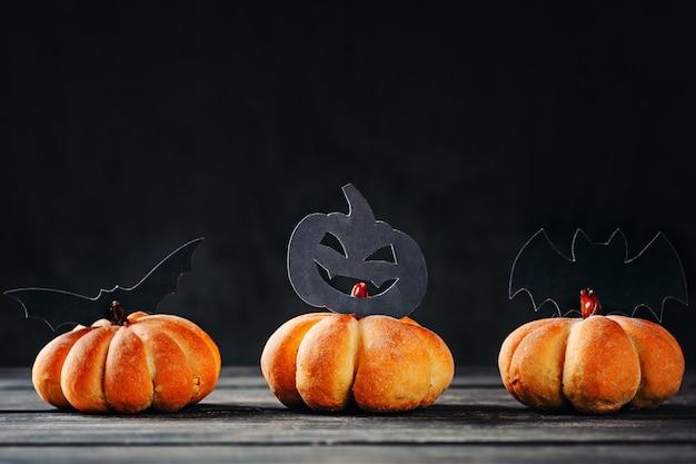 Selbst gemachtes halloween backt in form des kürbises auf dunklem hintergrund zusammen. hallo halloween süßigkeiten