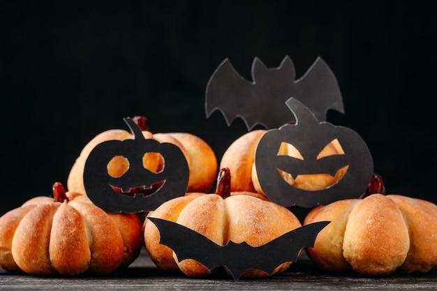 Selbst gemachtes halloween backt in form des kürbises auf dunklem hintergrund zusammen.