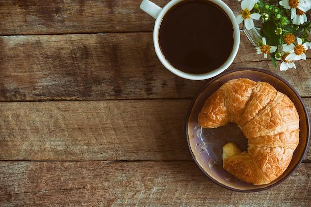 Selbst gemachtes hörnchen auf platte diente mit schwarzem kaffee oder americano zum frühstück