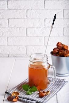 Selbst gemachtes kompott von trockenfrüchten in einem glas auf einem leuchtpult.