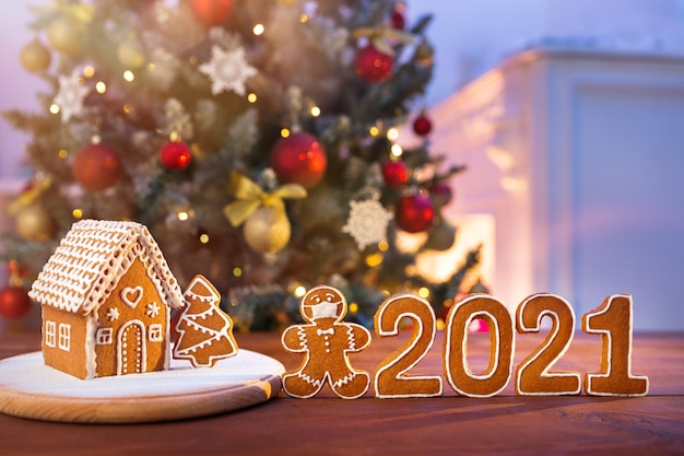Selbst gemachtes lebkuchenhaus auf dem hintergrund eines geschmückten weihnachtsbaumes und unscharfer lichter mit einem maskierten mannplätzchen und zahlen des neuen jahres