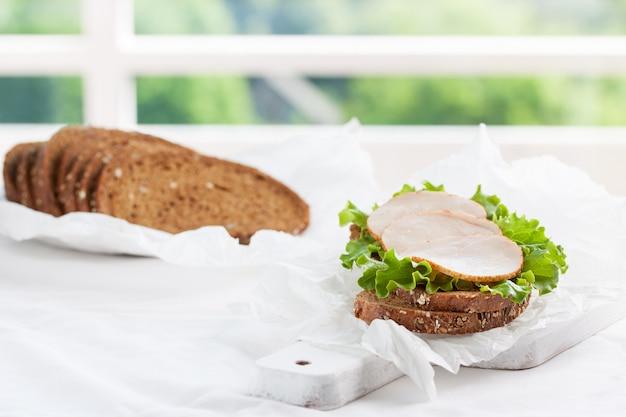 Selbst gemachtes leckeres sandwich mit salat und schinken auf einem schneidebrett