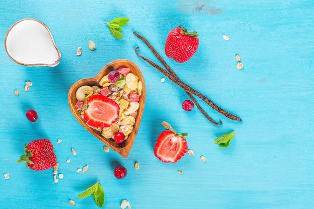 Selbst gemachtes müsli mit nüssen, kandierten früchten und beeren in einer herz-förmigen hölzernen schüssel auf einer blauen tabelle.