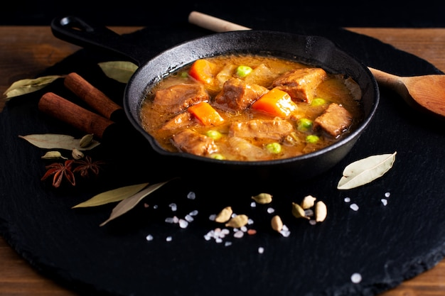 Selbst gemachtes organisches eintopfgericht vom winter-lebensmittelkonzept oder bourguignon in der gusseisen-bratpfanne