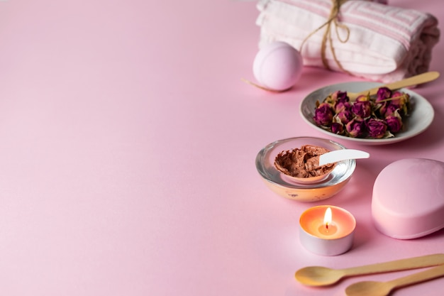 Selbst gemachtes peeling mit rosengeschmack und hautpflege mit natürlichen inhaltsstoffen auf rosa hintergrund mit tüchern, kerze und seife.