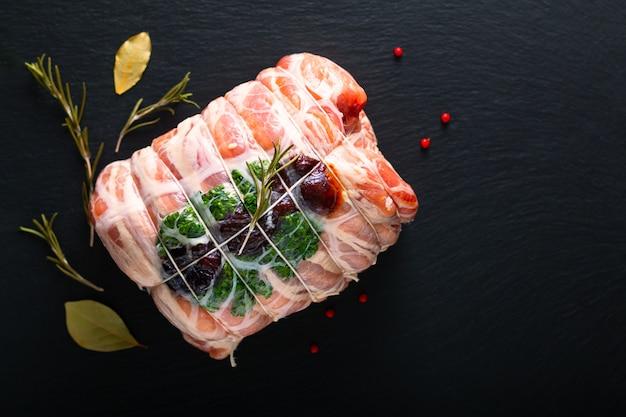 Selbst gemachtes rohes angefülltes schweinefilet des lebensmittelkonzeptes auf schwarzer schiefersteinplatte mit kopienraum