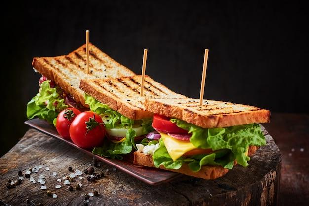 Selbst gemachtes sandwich mit schinken, kopfsalat, käse und tomate auf einem hölzernen hintergrund
