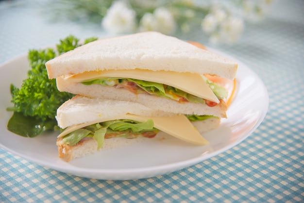 Selbst gemachtes sanwich frühstück stellte auf eine tabelle ein - gesetztes konzept des schnellimbissmorgens