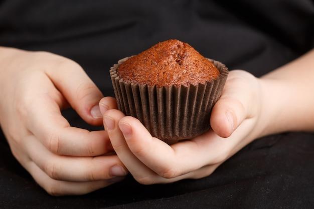 Selbst gemachtes schokoladenmuffin in den händen der kinder