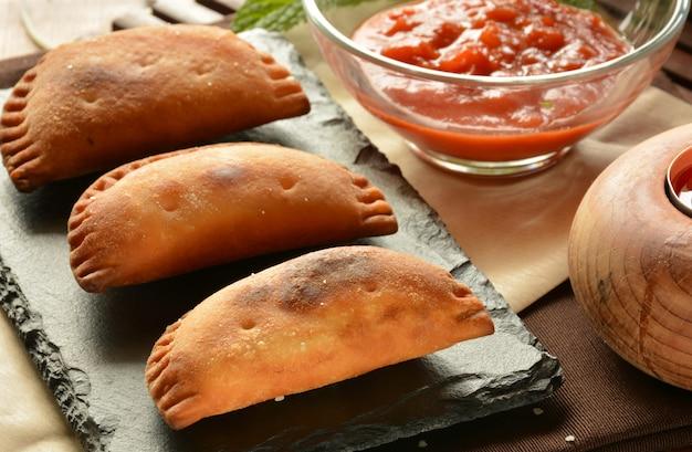 Selbst gemachtes thunfischpastetchen mit tomatensauce auf holztisch