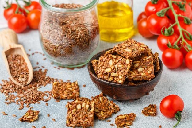 Selbst gemachtes vegetarisches (veganes) crackerleinsamen und -sonnenblume mit tomate