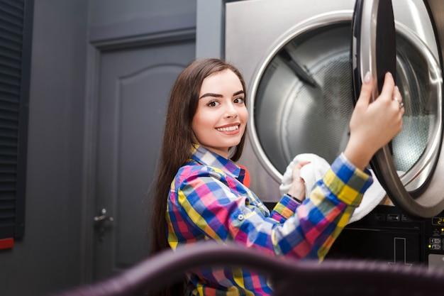 Selbstbedienungs-waschsalon client nimmt dinge aus dem trockner