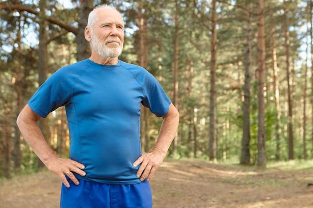 Selbstbestimmter älterer mann beim ruhestandstraining im freien in kiefernholz, händchen haltend an seinen hüften, übungen zum aufwärmen des körpers vor dem laufen. bärtiger pensionierter mann, der nach dem training luft holt