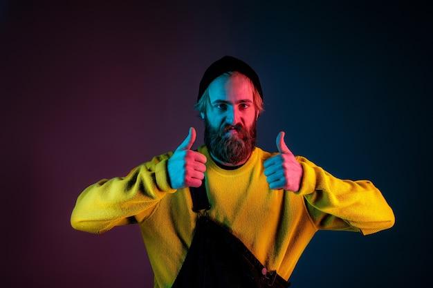 Selbstbewusst daumen hoch. porträt des kaukasischen mannes auf gradientenstudiohintergrund im neonlicht. schönes männliches modell mit hipster-stil. konzept der menschlichen emotionen, gesichtsausdruck, verkauf, anzeige.