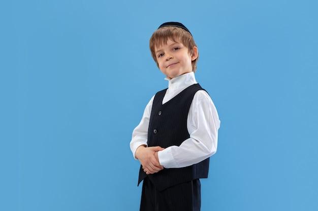 Selbstbewusst posieren, süß. porträt eines jungen orthodoxen jüdischen jungen lokalisiert auf blauer wand. purim, geschäft, festival, urlaub, feier pessach oder pessach, judentum, religionskonzept.