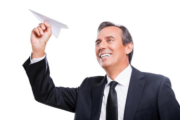 Selbstbewusst und erfolgreich. porträt eines selbstbewussten reifen mannes in formeller kleidung und brille, der in die kamera schaut und lächelt, während er vor weißem hintergrund steht