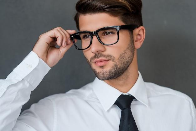 Selbstbewusst und gutaussehend. selbstbewusster junger geschäftsmann, der seine brille justiert und wegschaut