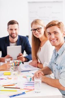 Selbstbewusst und kreativ. gruppe fröhlicher geschäftsleute in eleganter freizeitkleidung, die zusammen am tisch sitzen und in die kamera schauen