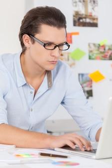 Selbstbewusst und kreativ. nachdenklicher junger mann im blauen hemd, der am computer arbeitet, während er an seinem arbeitsplatz sitzt