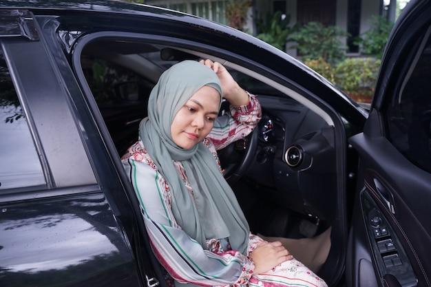 Selbstbewusst und schön. die rückansicht der attraktiven muslimischen frau in der freizeitkleidung lächelt beim autofahren.