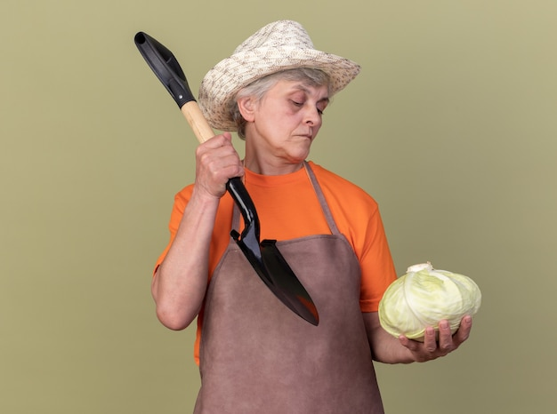 Selbstbewusste ältere gärtnerin, die einen gartenhut mit spaten trägt und kohl isoliert auf olivgrüner wand mit kopienraum betrachtet