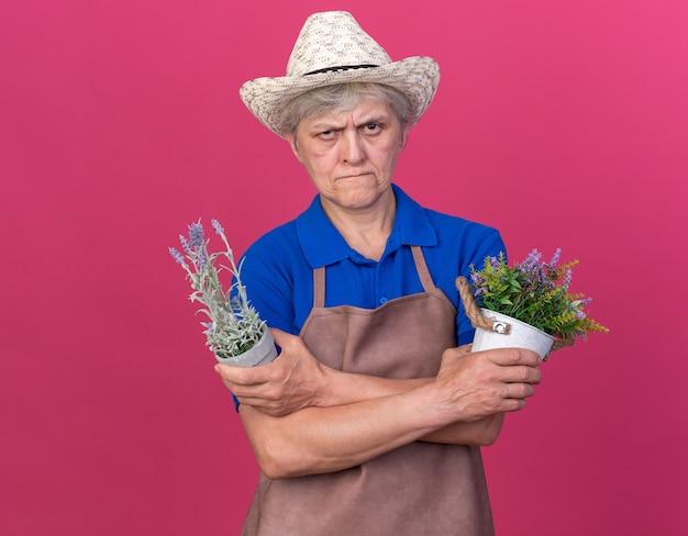 Selbstbewusste ältere gärtnerin mit gartenhut, die die arme kreuzt, die blumentöpfe isoliert auf rosa wand mit kopienraum halten