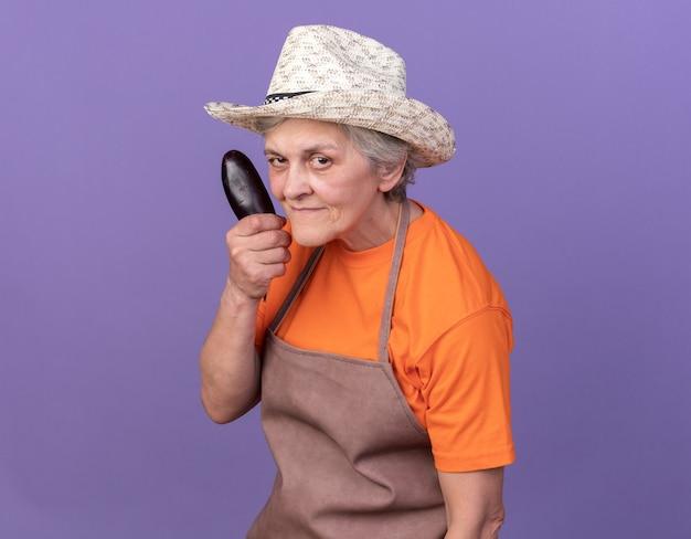 Selbstbewusste ältere gärtnerin mit gartenhut mit aubergine