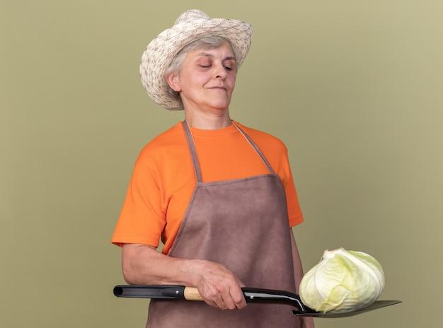Selbstbewusste ältere gärtnerin mit gartenhut mit kohl auf spaten