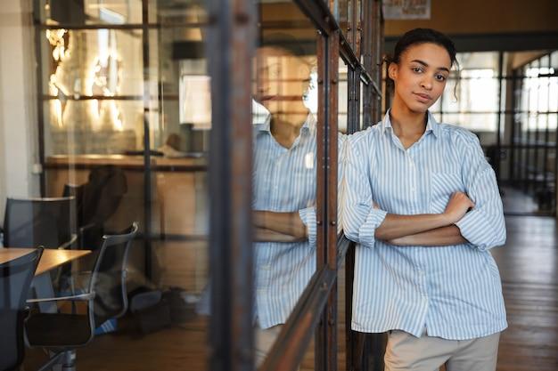 Selbstbewusste afroamerikanische frau posiert mit verschränkten händen, während sie sich in einem modernen büro an eine glaswand lehnt