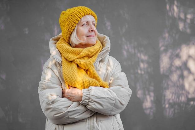 Selbstbewusste alte frau im warmen mantel mit stilvollem strickschal und mütze, die die arme verschränkt