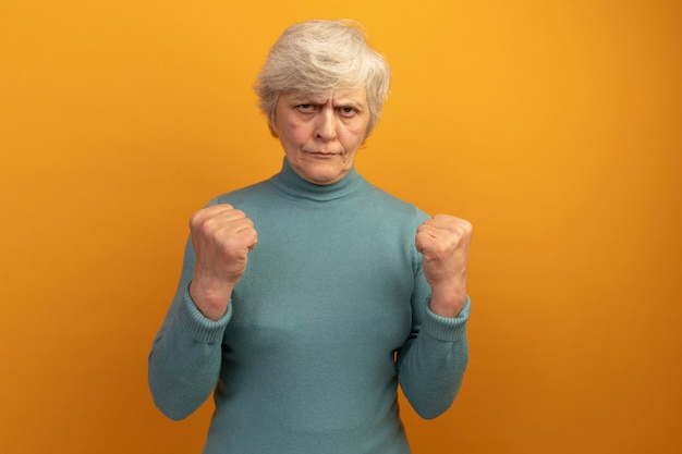 Selbstbewusste alte frau mit blauem rollkragenpullover, die auf die geballten fäuste blickt und eine starke geste einzeln auf oranger wand mit kopierraum macht