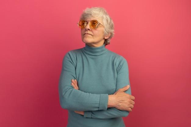 Selbstbewusste alte frau mit blauem rollkragenpullover und sonnenbrille, die mit geschlossener haltung steht und auf die seite isoliert auf rosa wand mit kopierraum schaut