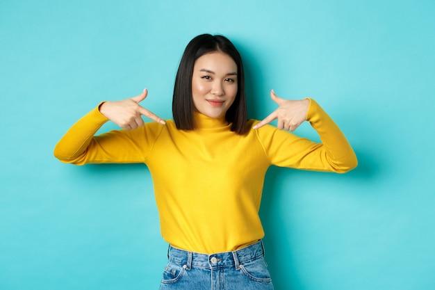Selbstbewusste asiatische frau in stylischem pullover, die mit den fingern auf das logo in der mitte zeigt, selbstbewusst in die kamera lächelt und auf blauem hintergrund steht