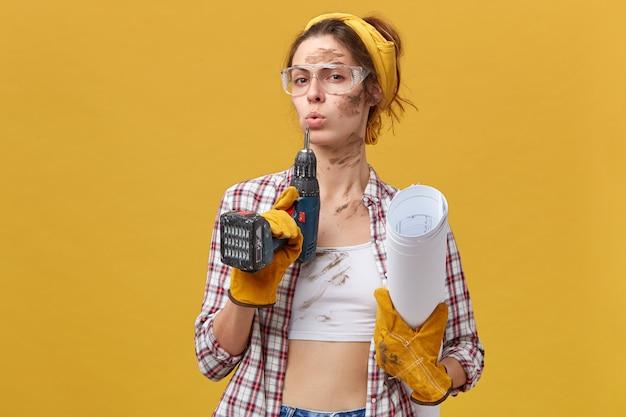 Selbstbewusste baumeisterin, die eine schutzbrille, ein weißes oberteil und ein kariertes hemd trägt, schutzhandschuhe, die bohrer halten, und papiere, die nach harter arbeit schmutzig sind, isoliert über gelber wand. instandhaltung